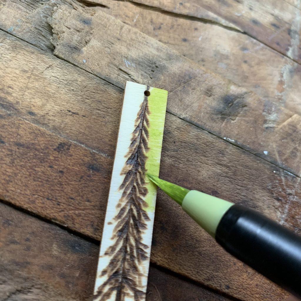Wood Burned Earring tutorial step 4 add color fine tip watercolor brush pen on wood